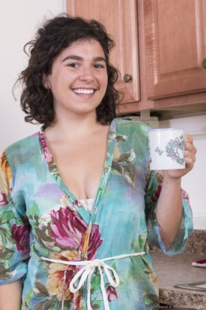 Serai enjoys coffee and then strips in kitchen